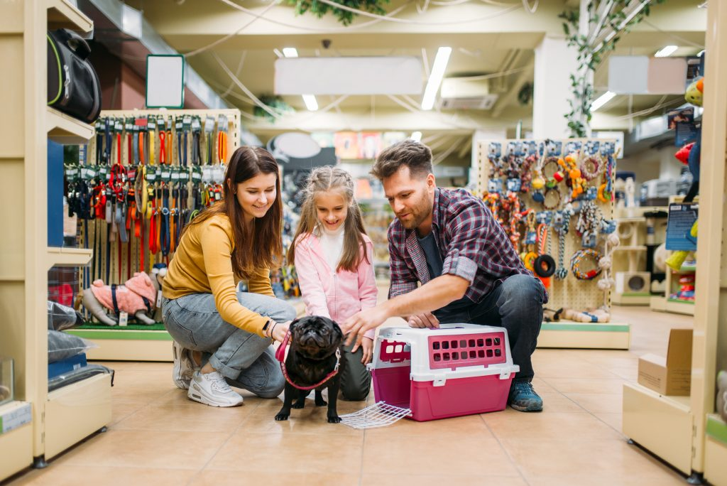 Family buying supplies with dog in pet store