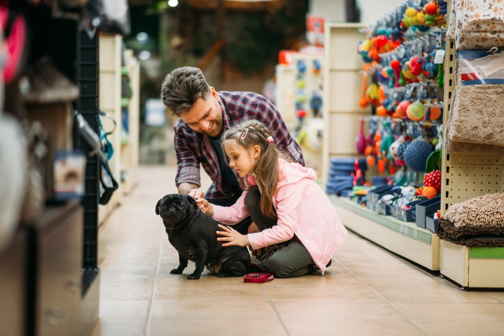 Dad with daughter and dog in pet store