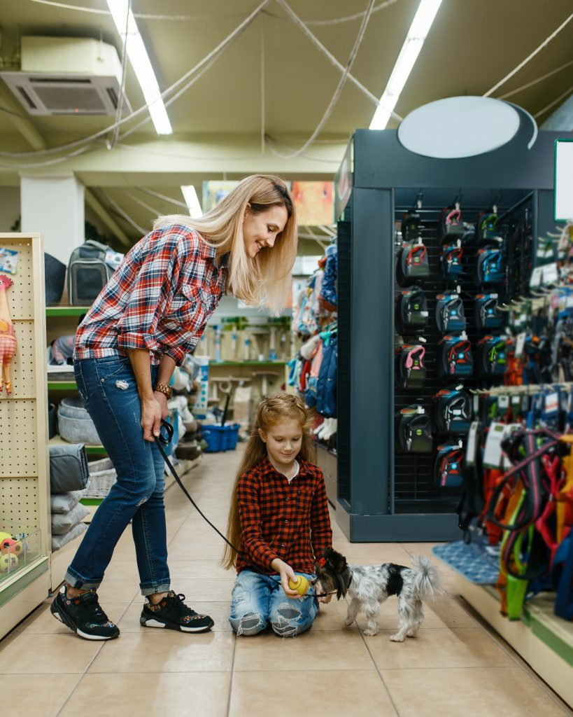 Mother with daughter and dog in pet store